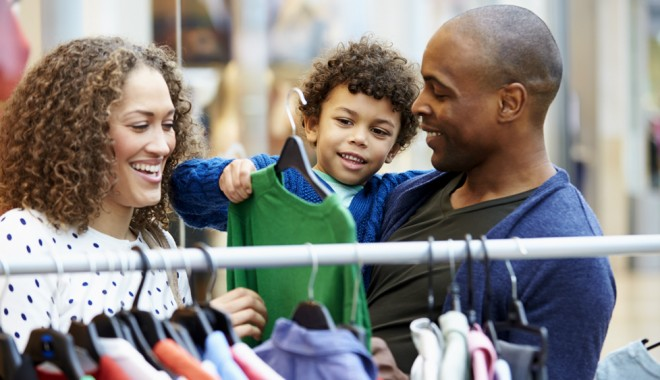 A mother, father and young son browsing a rail of clothes.