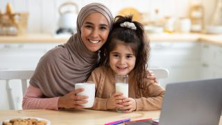 A woman in a hijab sitting at the table with her daughter on lap, smiling. Laptop on the table.